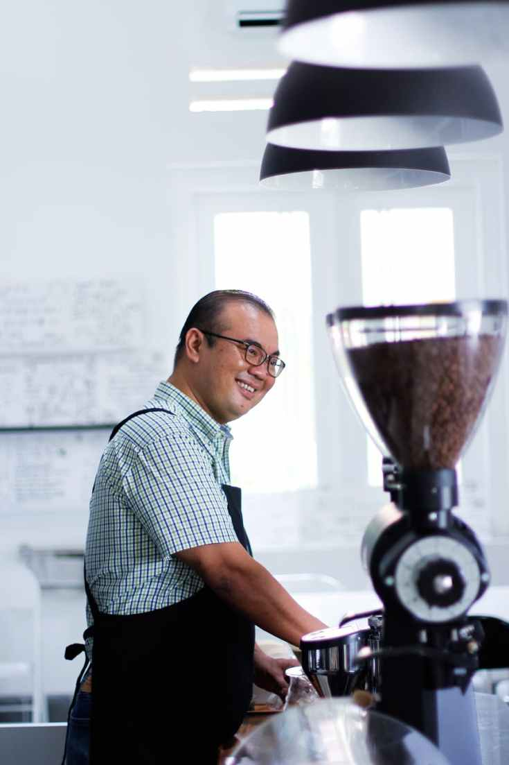 man wearing plaid t shirt and black apron in front of coffeemaker